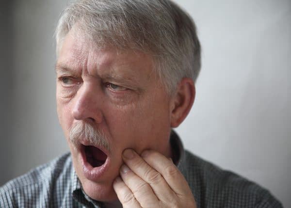 older man showing jaw pain
